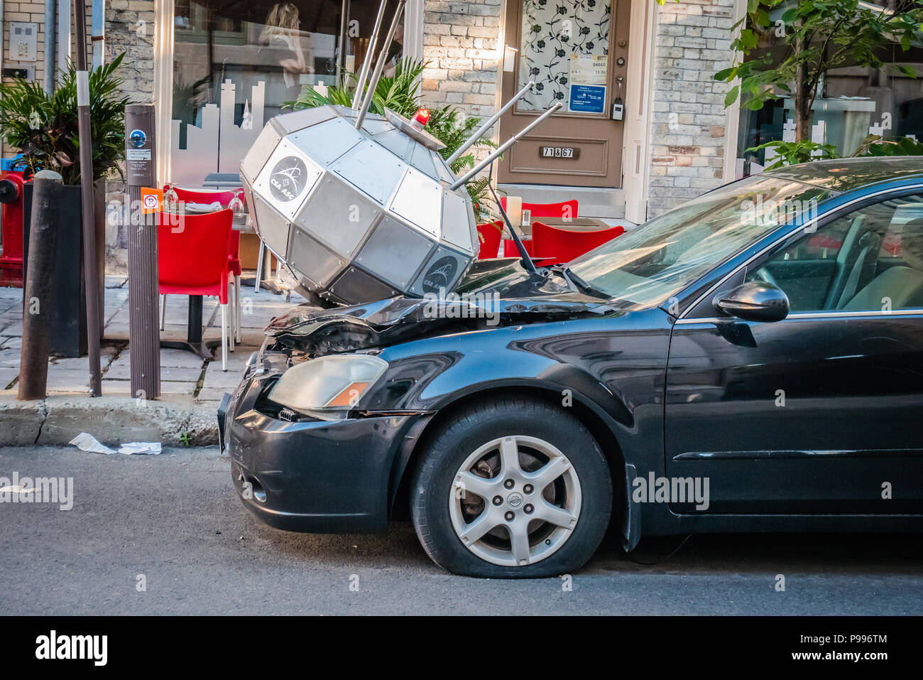 A silver object damaged the front of a black car - Stock Image