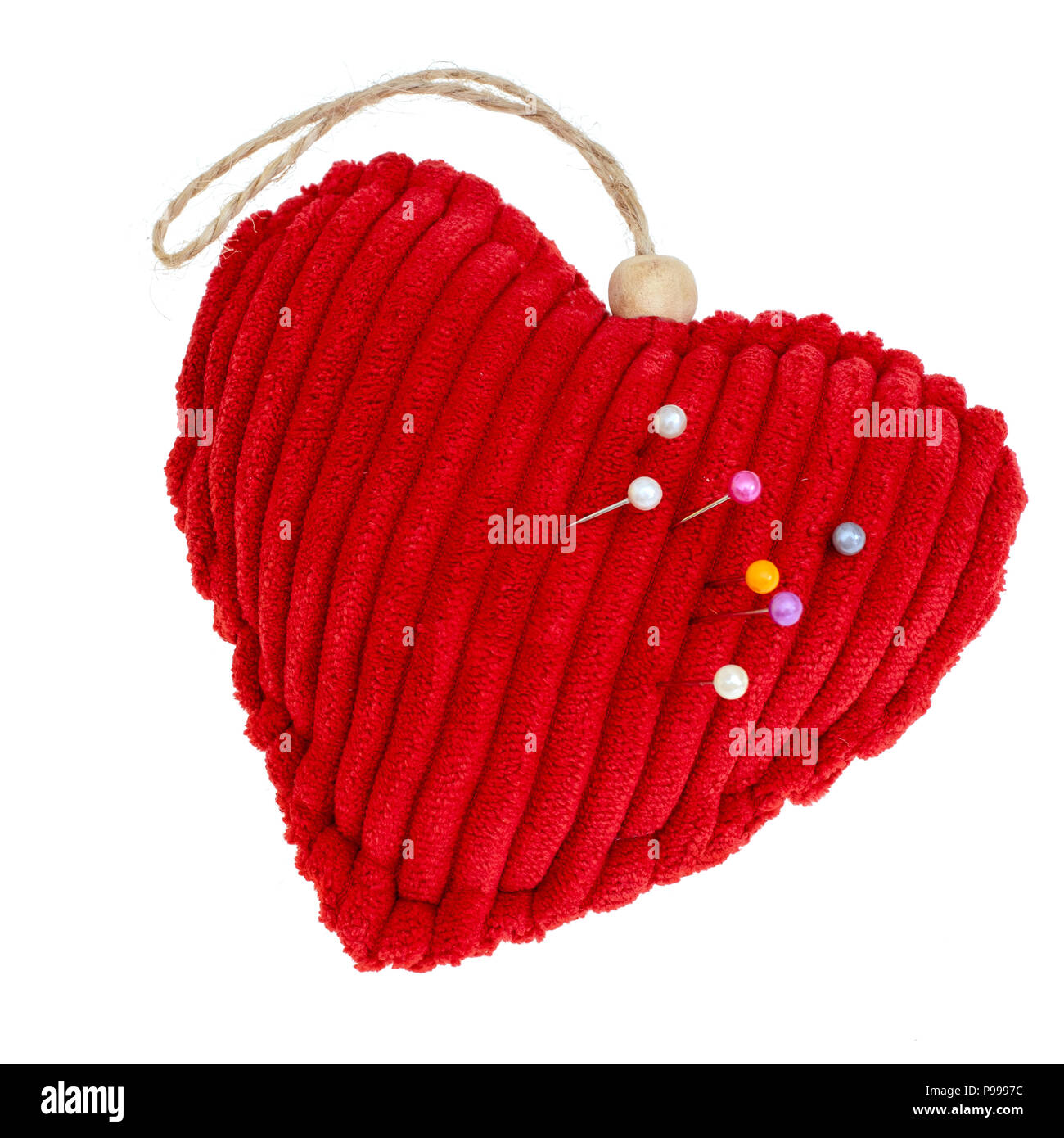 Red cord fabric heart shape pincushion isolated on white. With pins. - Stock Image