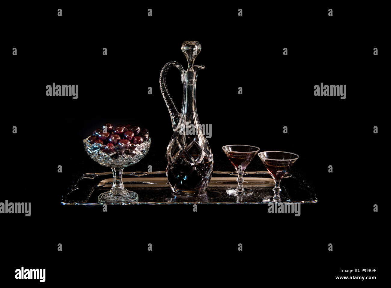 Cherries on an old crystal bowl and a crystal carafe and glasses with cherry brandy on a silver dish with a black background, a still life. - Stock Image