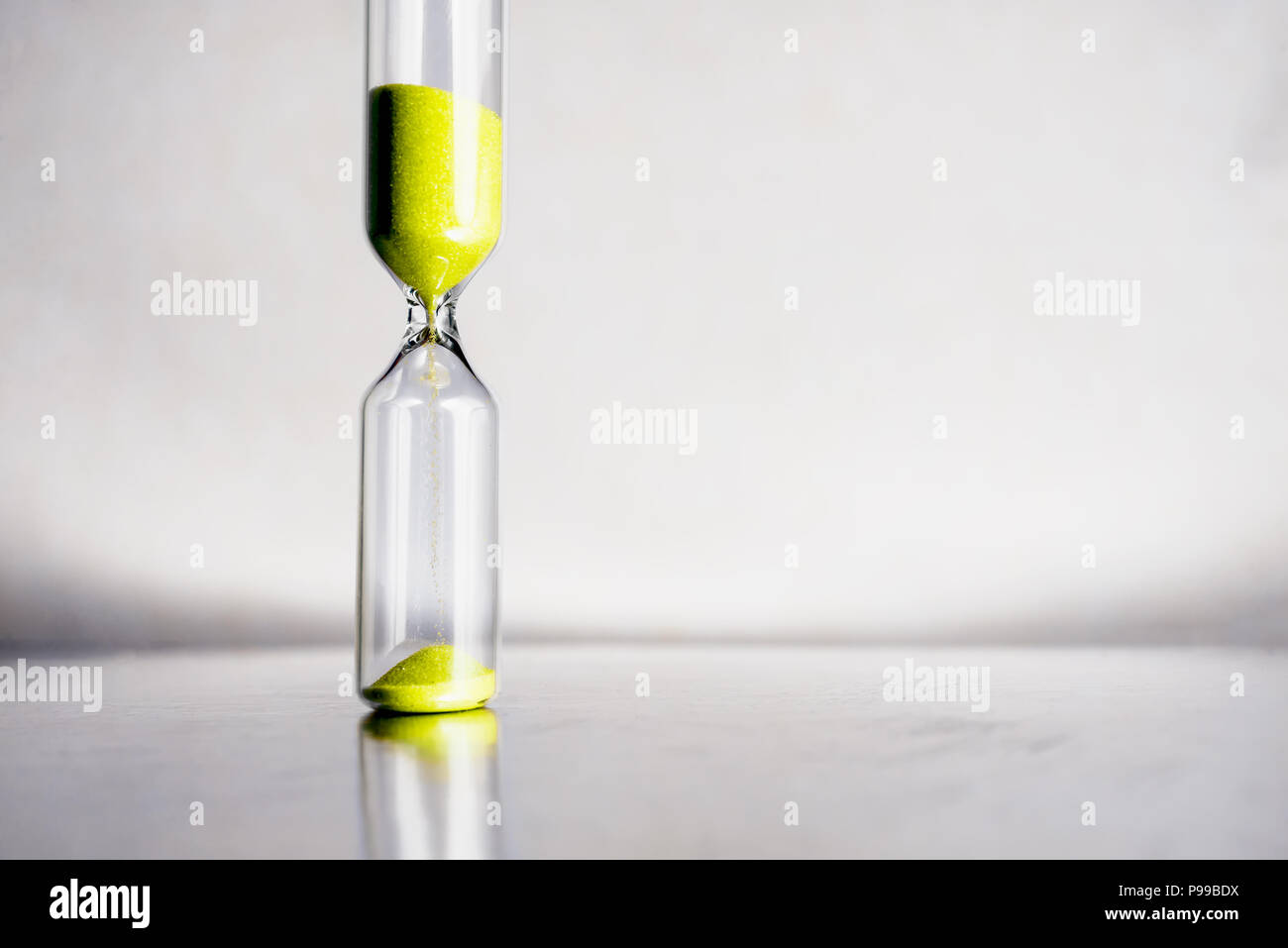 Modern beautiful yellow hourglass with bright background for copy space. Hourglass time passing concept for business deadline, urgency and running out of time. - Stock Image