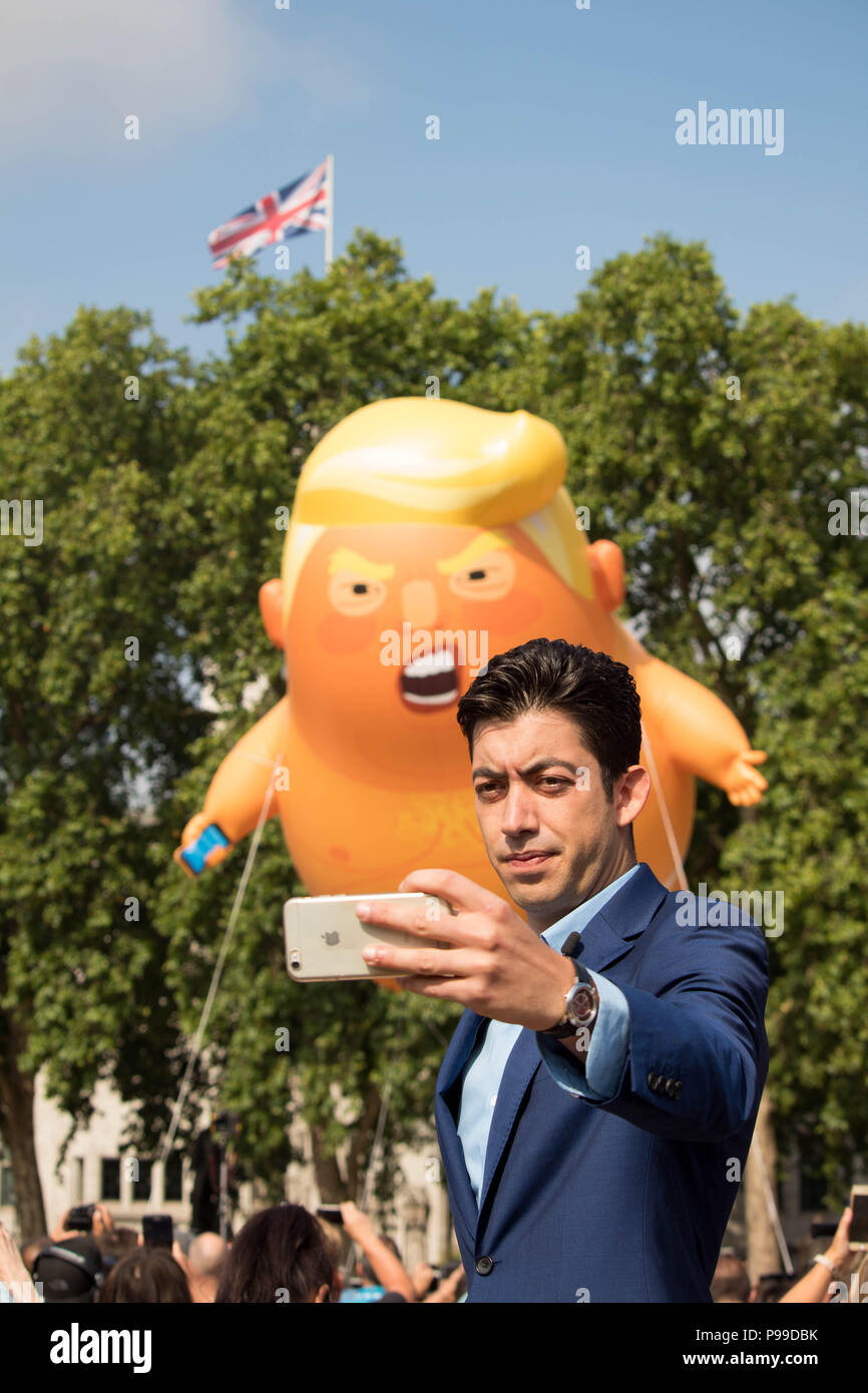 News presenter pausing for selfie a'STOP TRUMP' protests, Parliament Square Gardens as the 'Trump Baby' giant inflatable rises. London, UK 13/7/18. - Stock Image