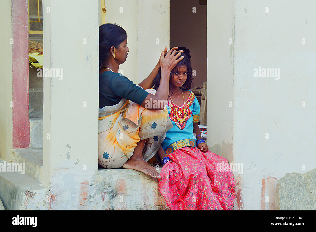 Mother checking for head lice at daughter, Mother combing daughter, care about hairstyle. Stock Photo