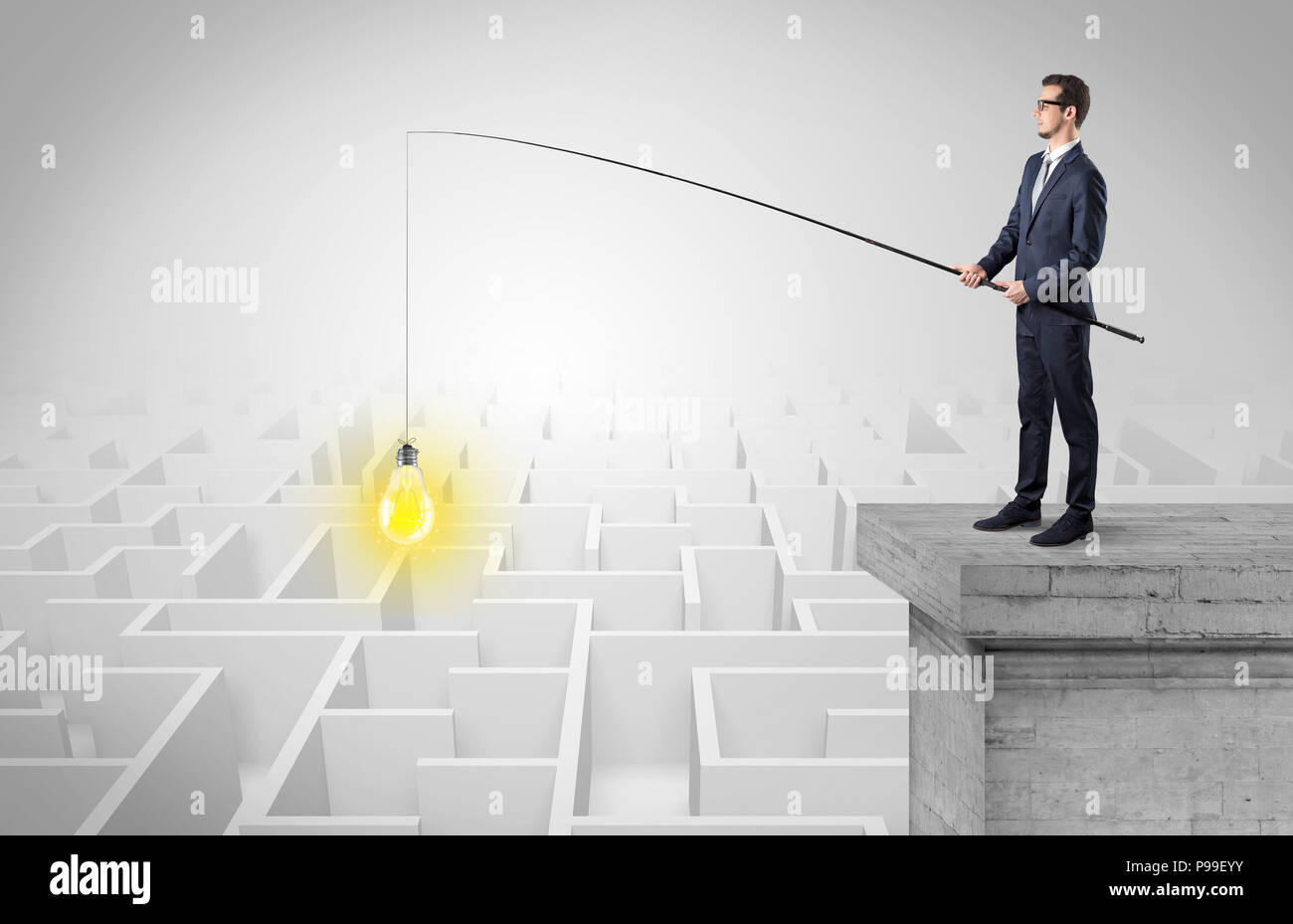 Young businessman fishing new idea concept on the top of a building from a maze - Stock Image