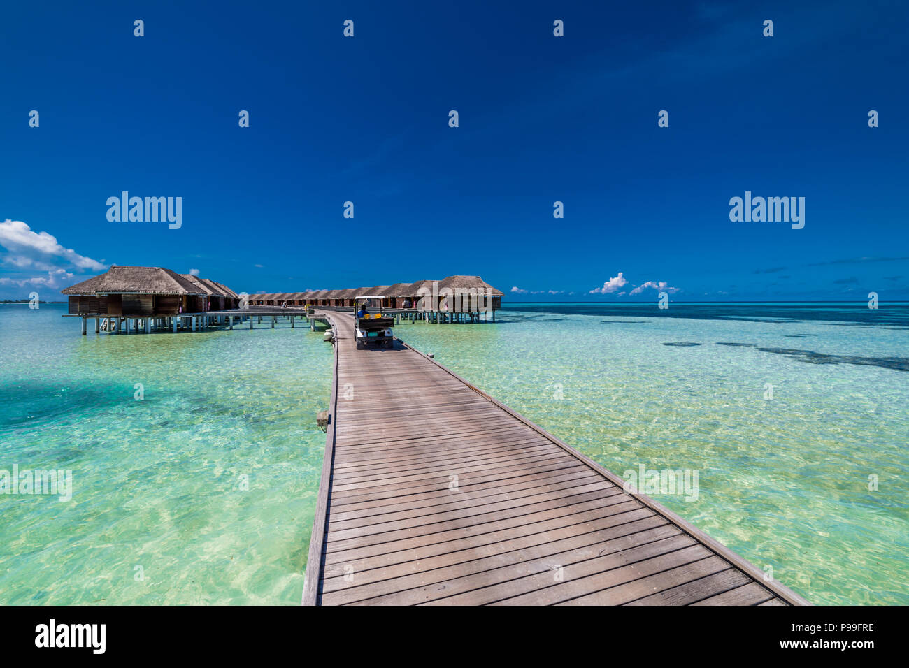 Maldives island, luxury water villas resort and wooden pier. Beautiful sky and clouds and beach background for summer vacation holiday and travel - Stock Image