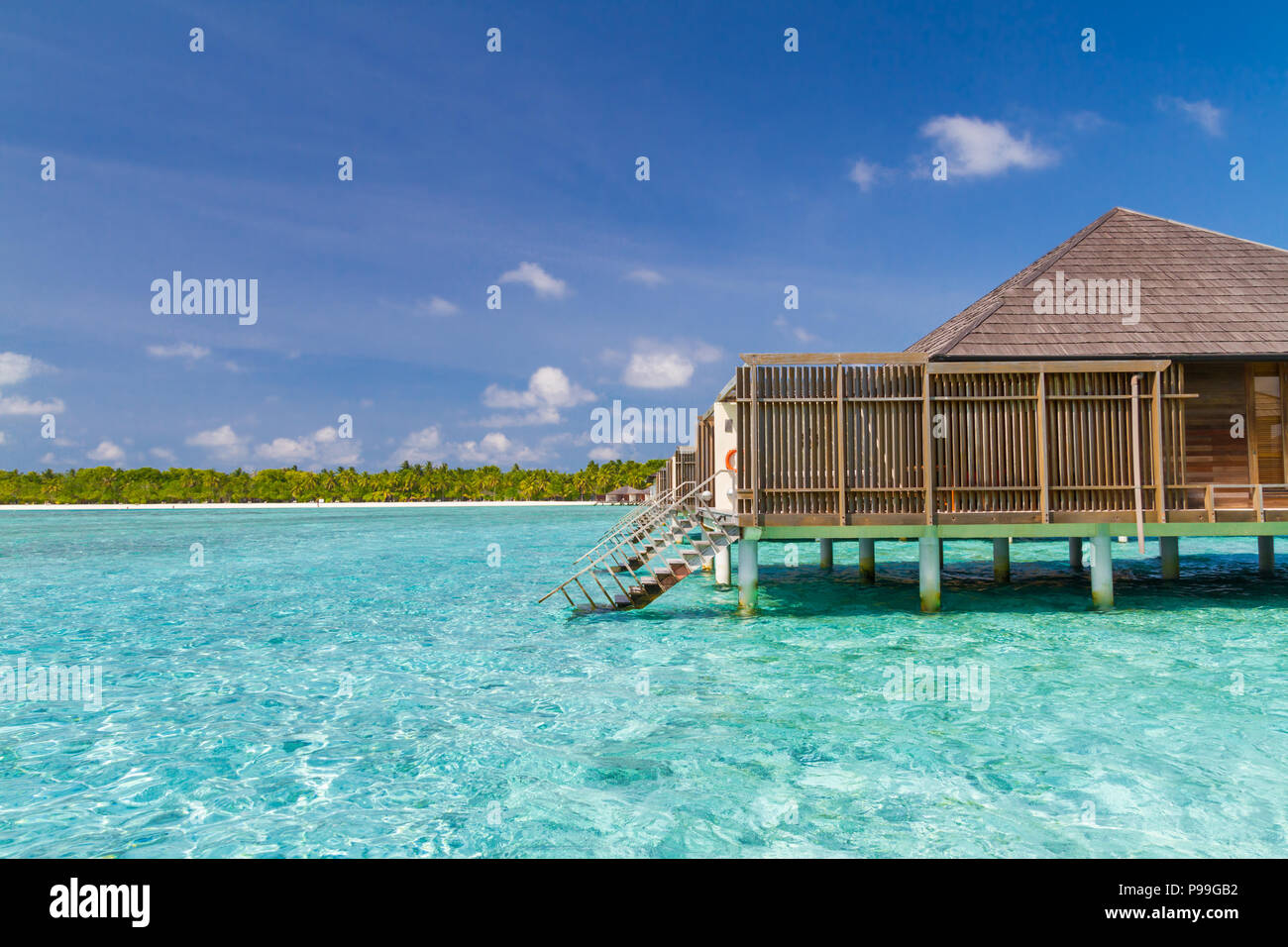 Luxury over water bungalow and villas side view with beautiful blue sea and lagoon - Stock Image