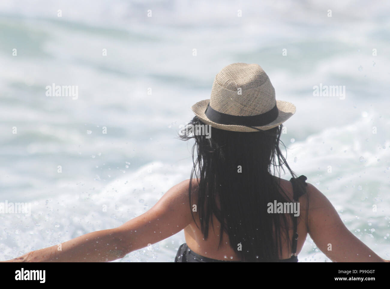 Beautiful girl, seen from behind, with hat who look the sea. Sea in the background. Sabaudia, Lazio, Italy - Stock Image