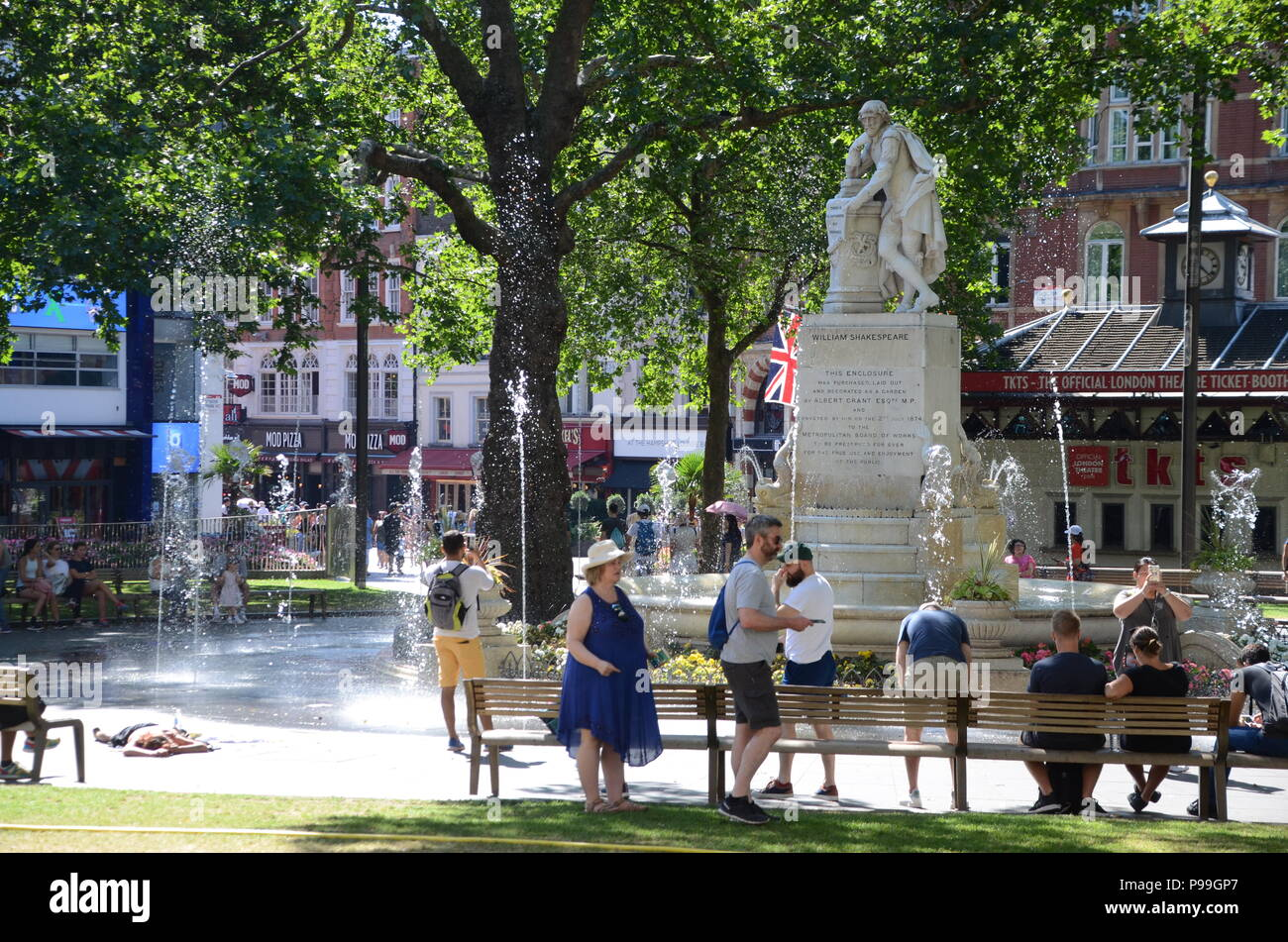 a homeless woman passed out in leicester square gardens london with tourists 2018 - Stock Image