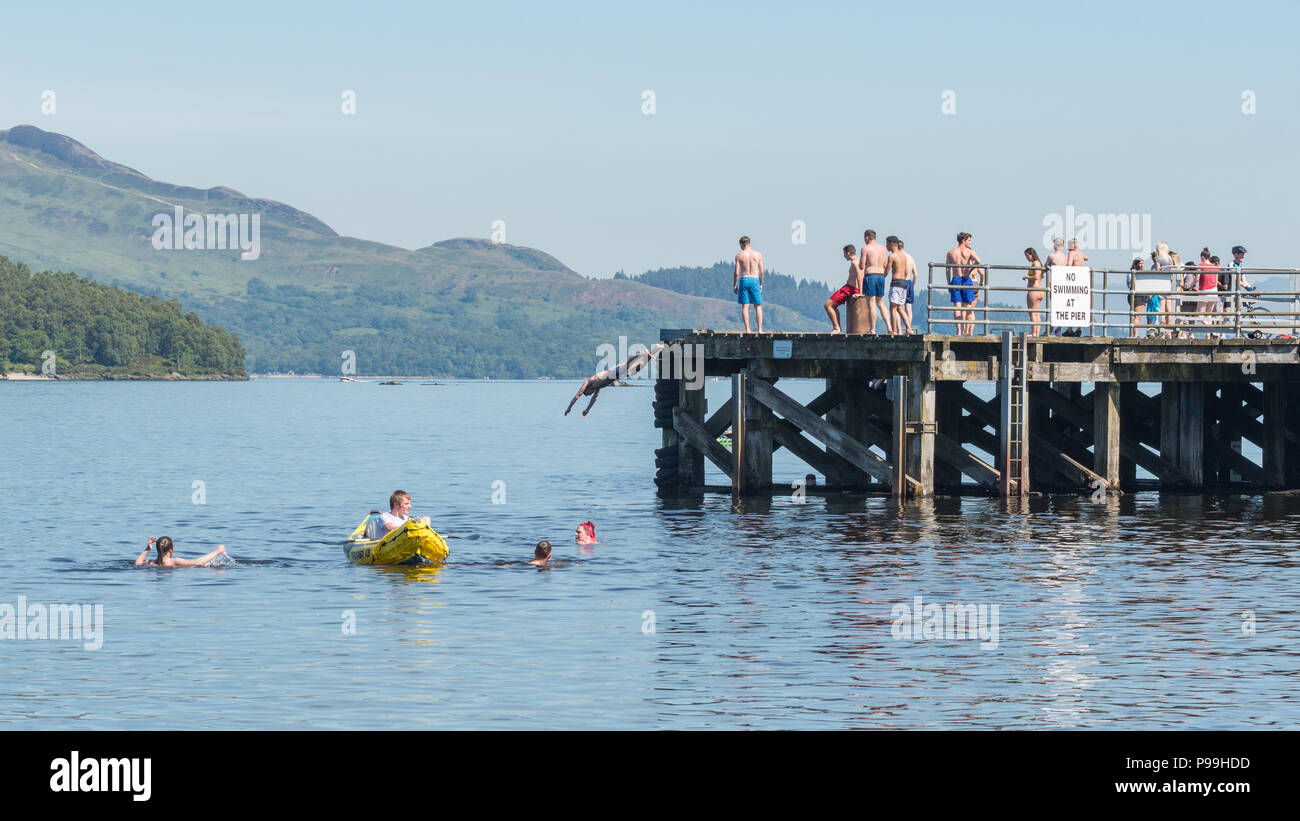young people enjoying an unusually hot day at Luss, Loch Lomond - swimming, paddling and diving off the pier during the June/July 2018 heatwave - Stock Image