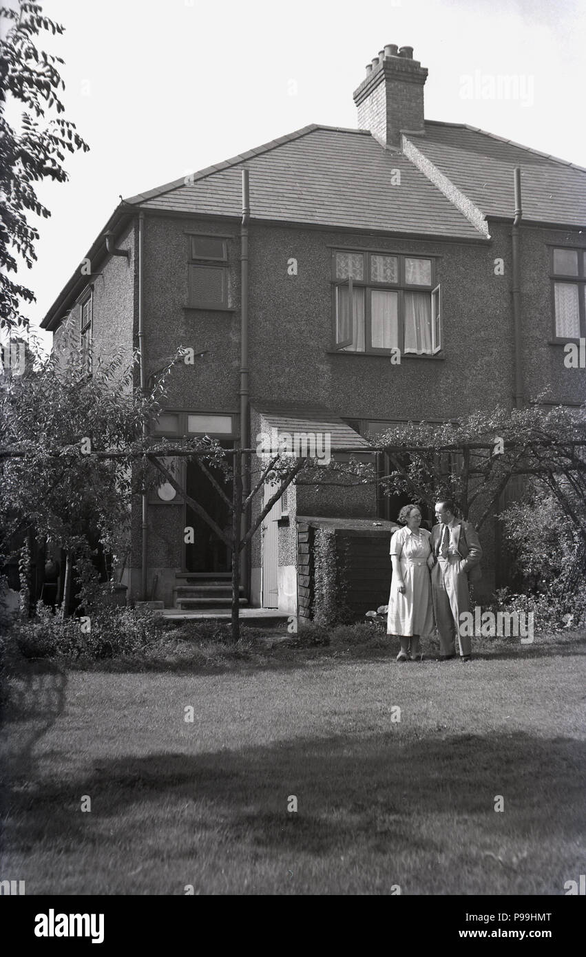 1950s, a man and woman standing togther outside in the back garden of a large semi-detached suburban house, England, UK. - Stock Image