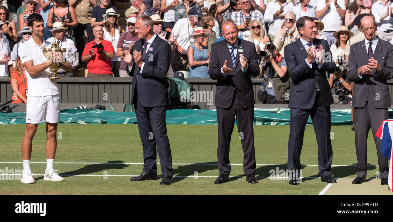 Wimbledon London 2018. Novac Djokovic wins Wimbledon for fourth time. In the photo he holds his trophy on centre court next to line up of officials - Stock Image