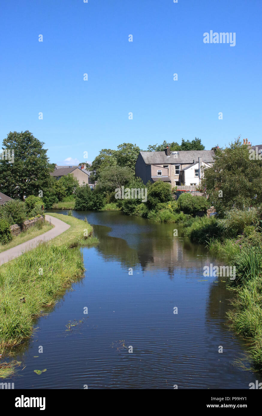 View along the Lancaster canal and towpath from Shaw Street bridge in the Freehold area of Lancaster, Lancashire, England. - Stock Image