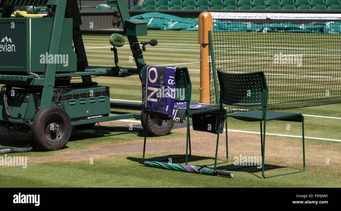 Players' chairs with towel folded over the back, and a green and purple umbrella on the ground. Towel has the name of Djokovic on it. - Stock Image