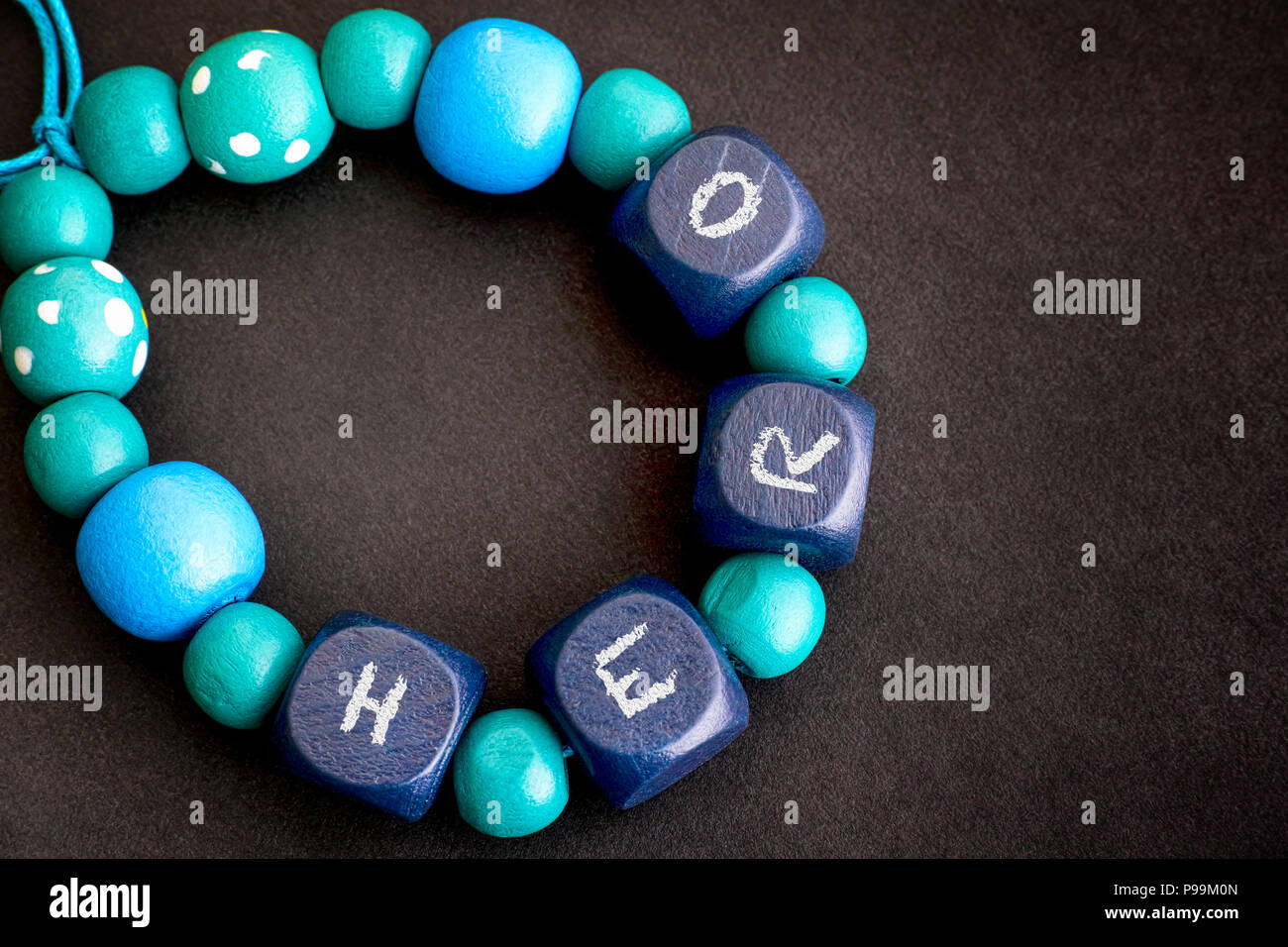 Bracelet of blue wooden beads with word HERO on black background. Close-up. - Stock Image