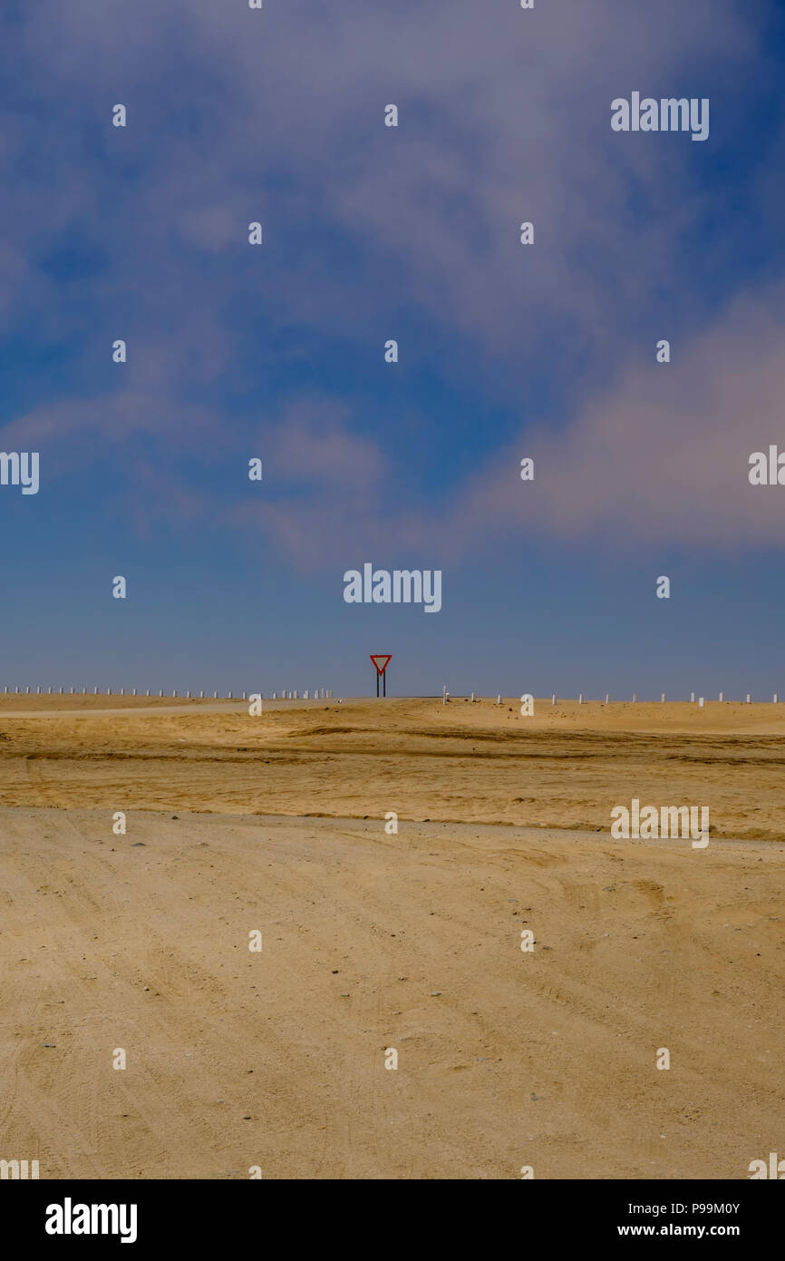 Yield sign on empty road in barren landscape of Namib Desert in Namibia - Stock Image