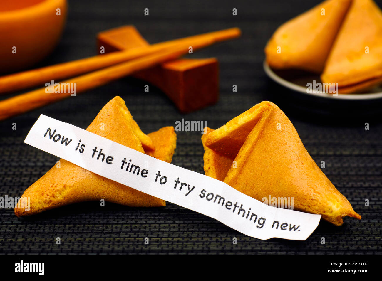 Paper strip with phrase Now is the Time to Try Something New from fortune cookie, another cookie and chopsticks on black napkin background. - Stock Image