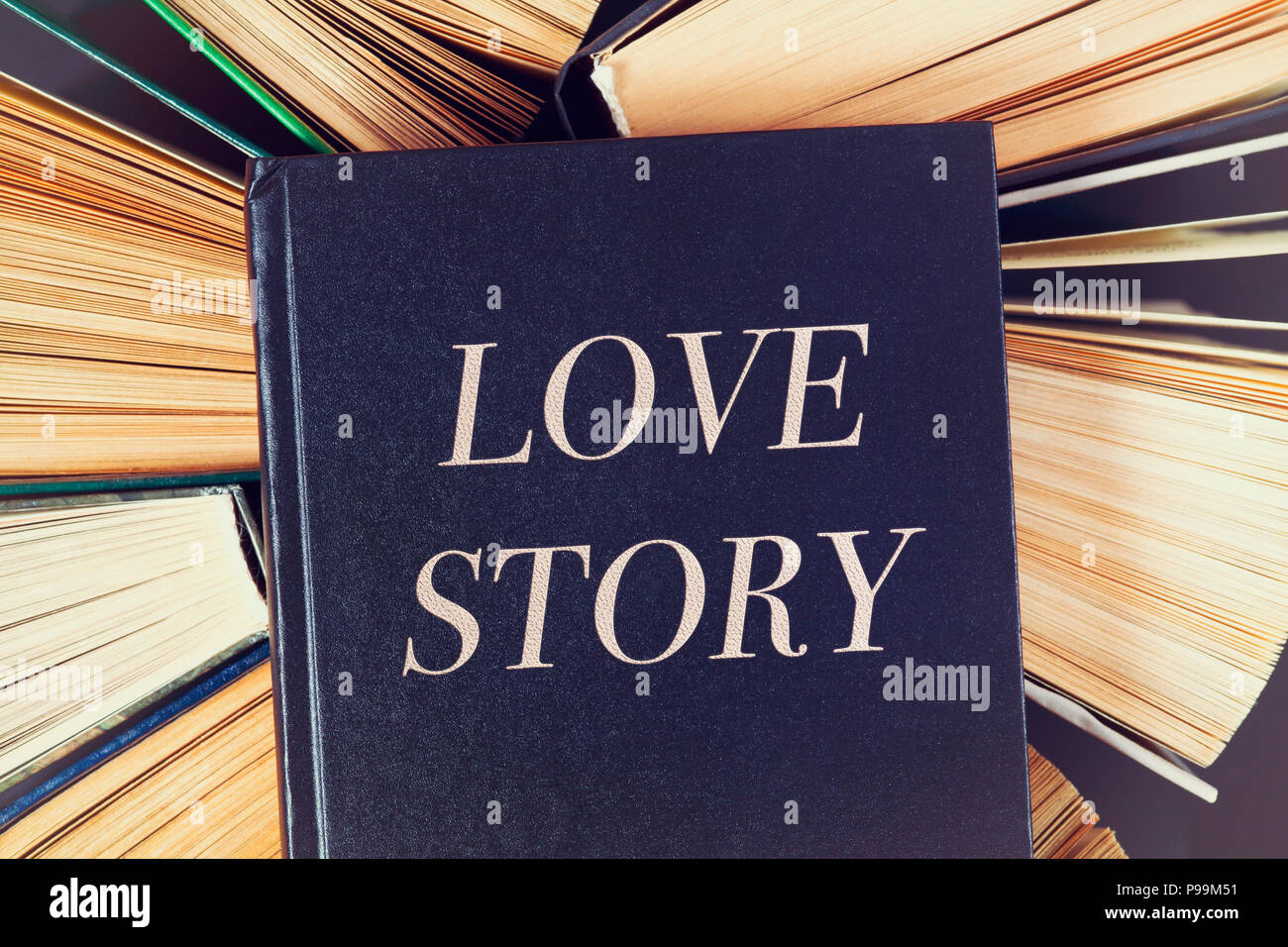 Top view of old hardcover books with book Love Story on top. - Stock Image