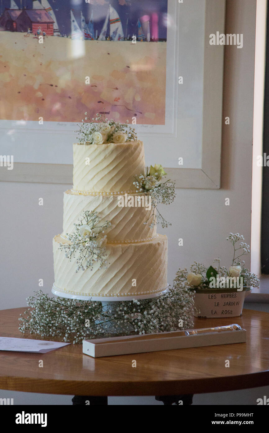 Three tiered wedding cake covered in buttercream icing and real flowers - Stock Image