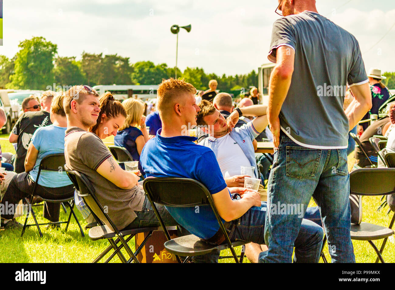 Group of young men drinking outside in the sunshine at the Northumberland County Show, May 2018. - Stock Image