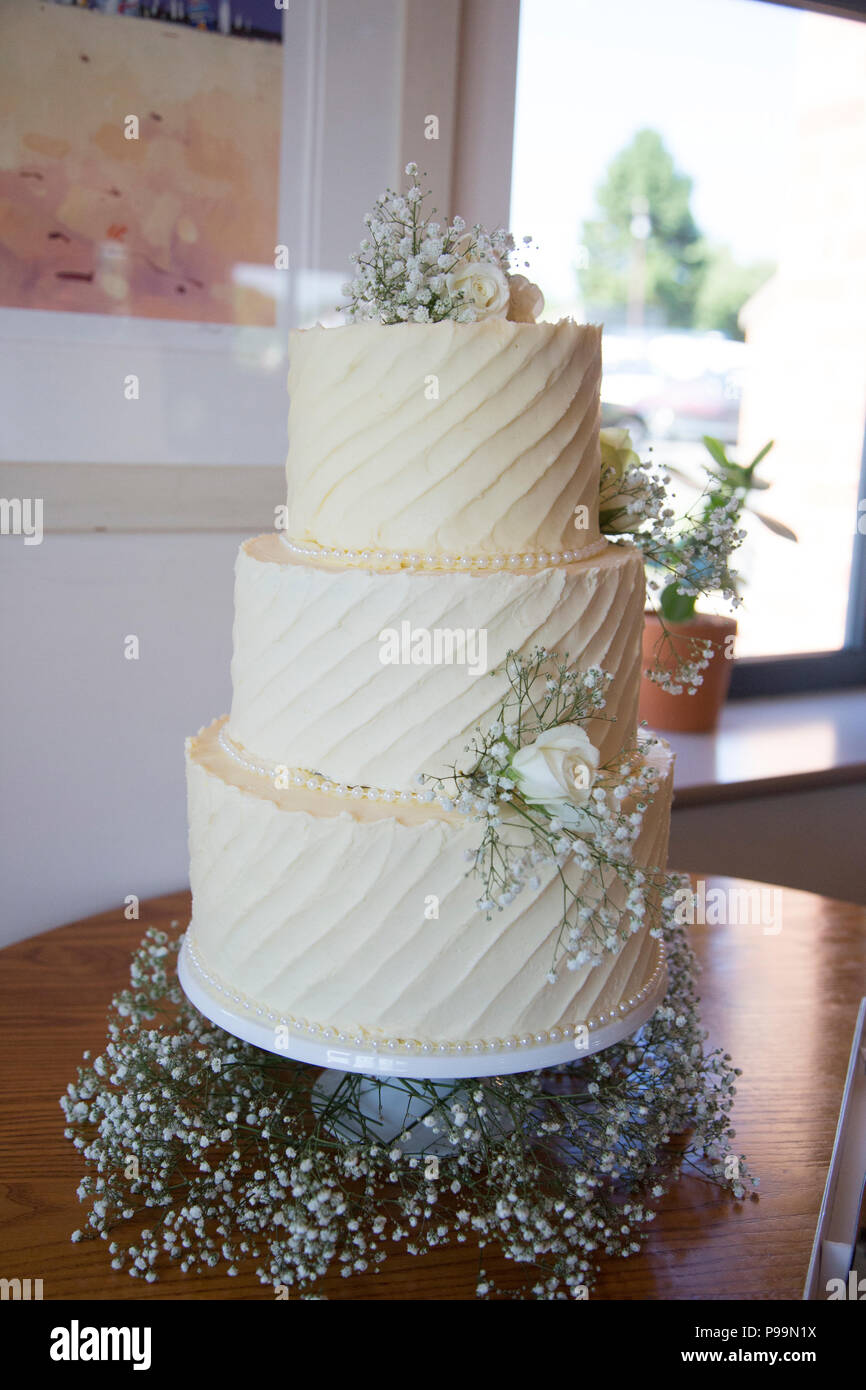 Wedding cake covered in cream butter icing decorated with real flowers and greenery - Stock Image
