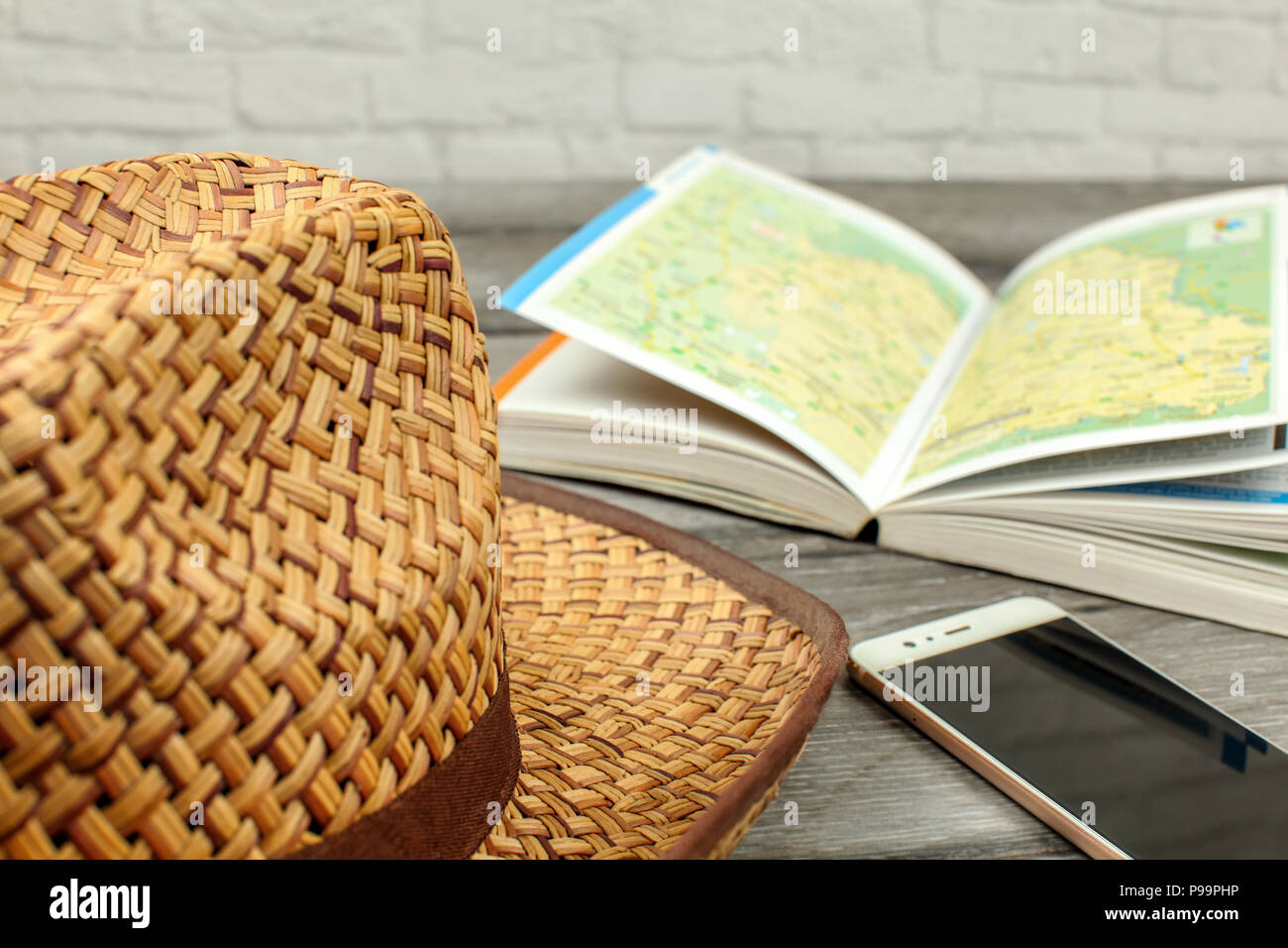 Straw hat, guide book with map, and mobile phone on gray wood desk. Travel planning concept. - Stock Image