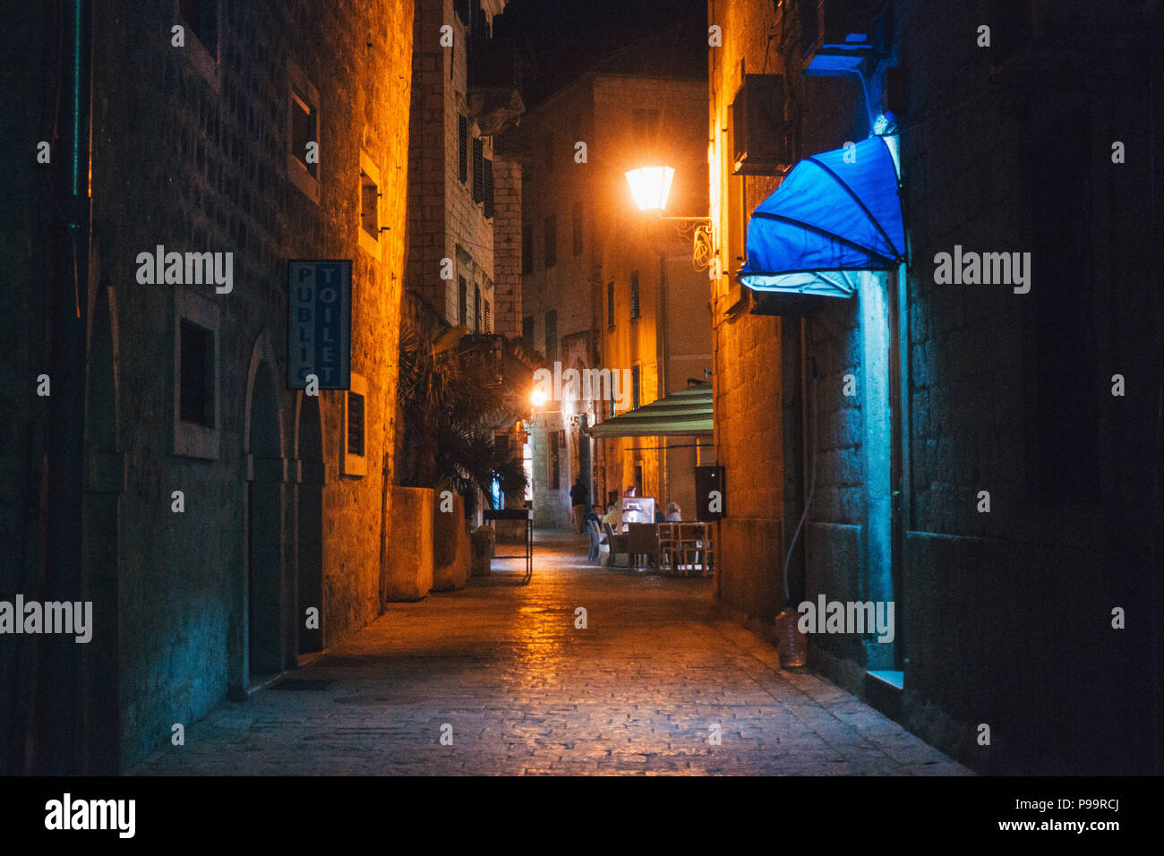 a deserted narrow cobblestone street at night in Kotor Old Town, Montenegro - Stock Image
