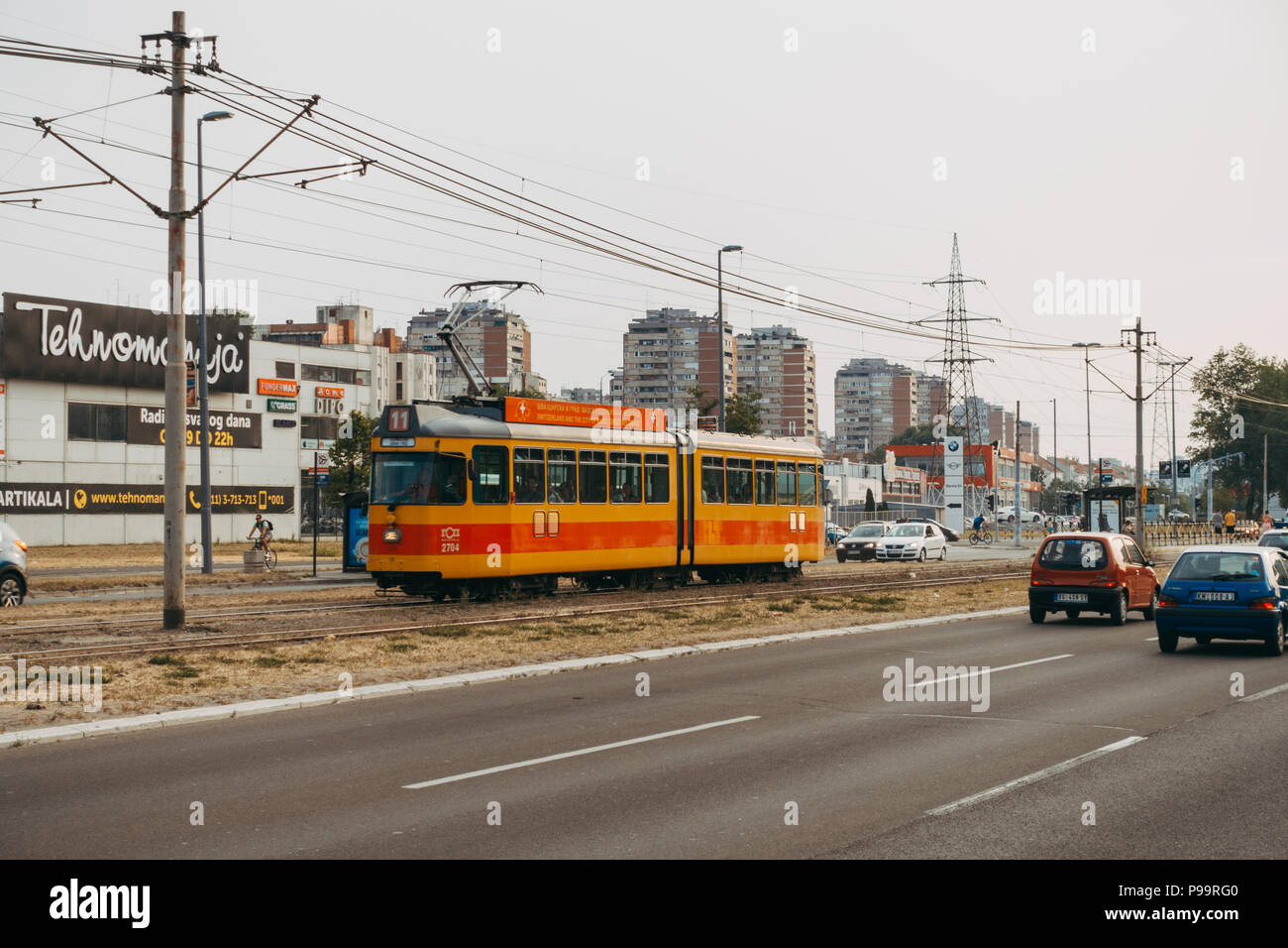 A tram passes traffic in the median of a trunk road in Belgrade, Serbia - Stock Image