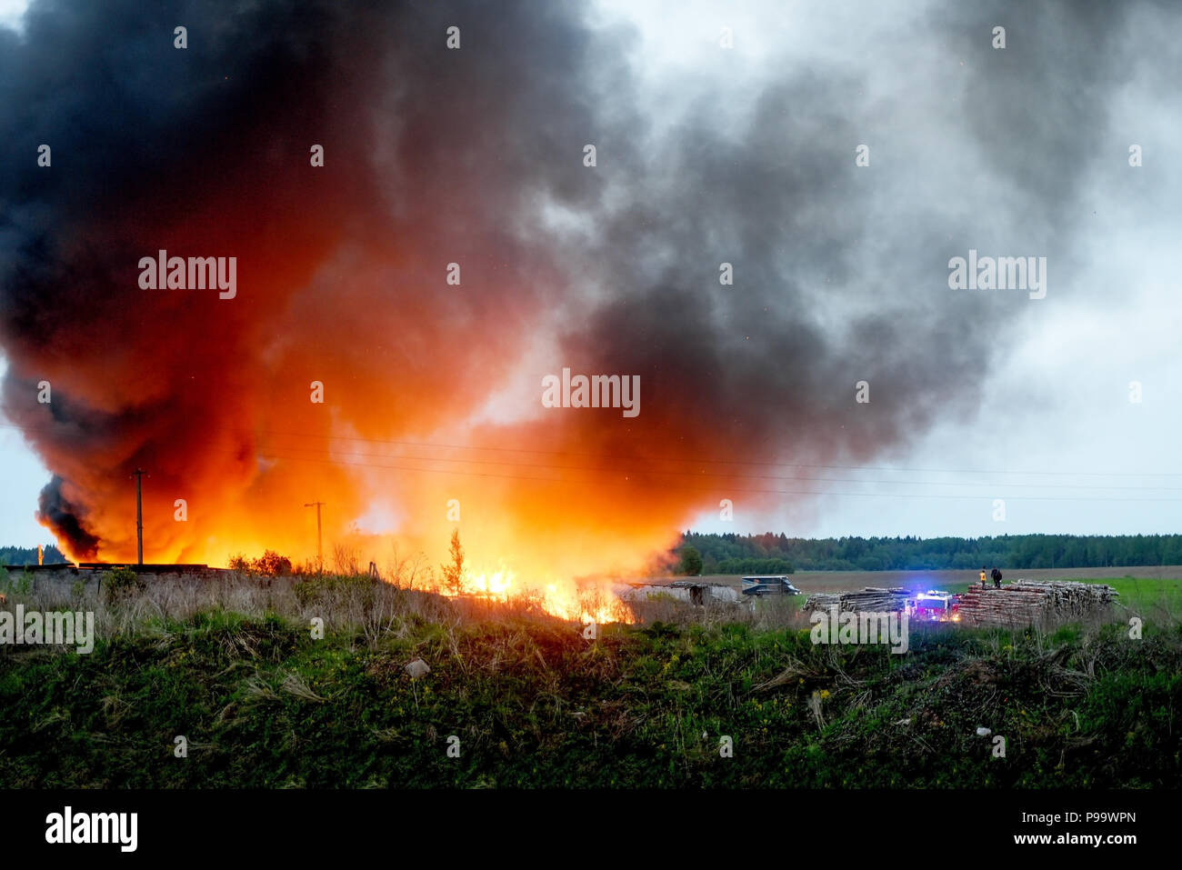 Firefighters extinguish the fire in the village, hot weather and the concept of safety - Stock Image