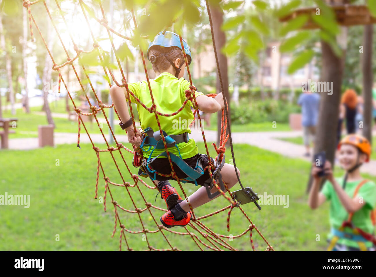 Little boy in safety equipment climbing on rope wall at adventure park. Fiend making a photo shot on smartphone. Children summer sport extreme outdoor - Stock Image