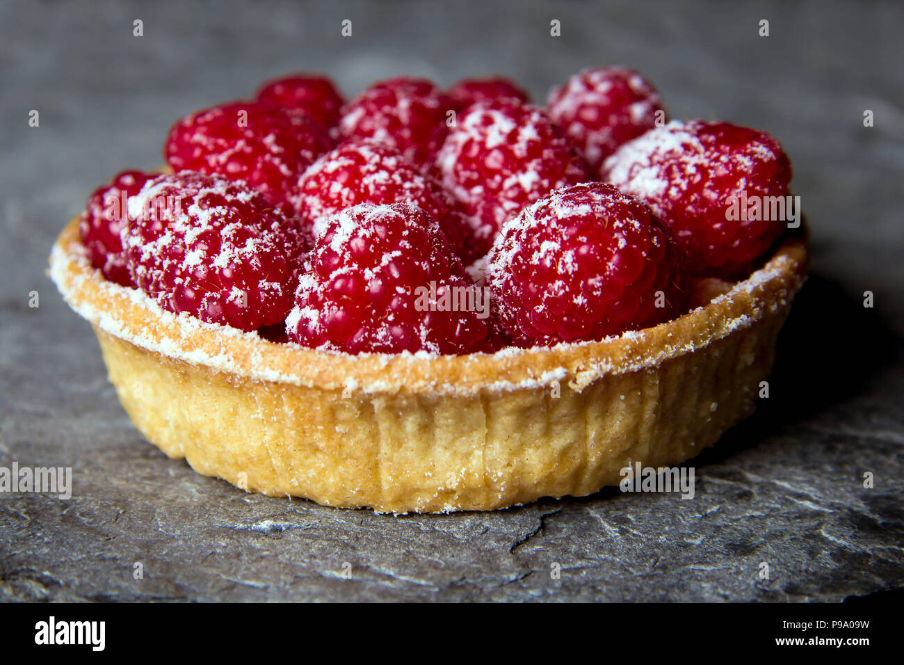 Raspberry tart made with shortcrust pastry dusted with icing sugar presented on a Cornish slate surface. - Stock Image