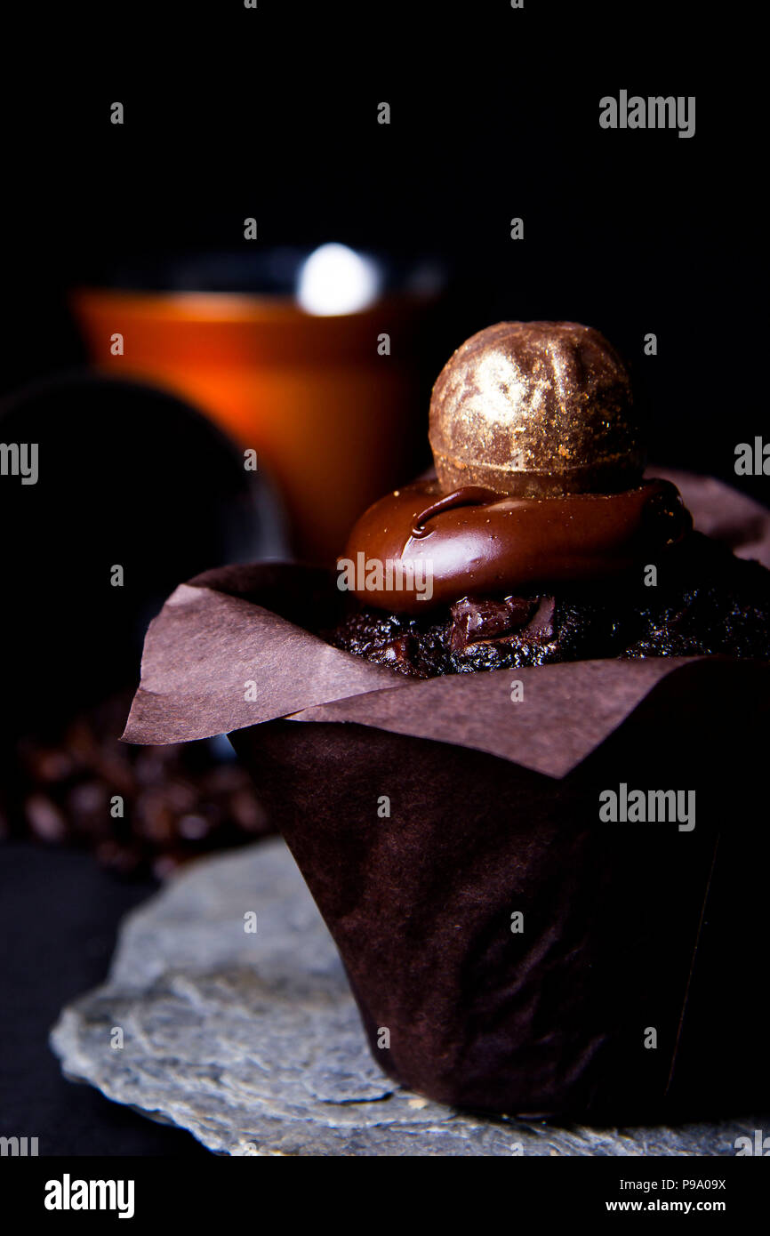 Chocolate muffin topped with smooth chocolate frosting and gold handmade confectionery presented on a Cornish slate - Stock Image