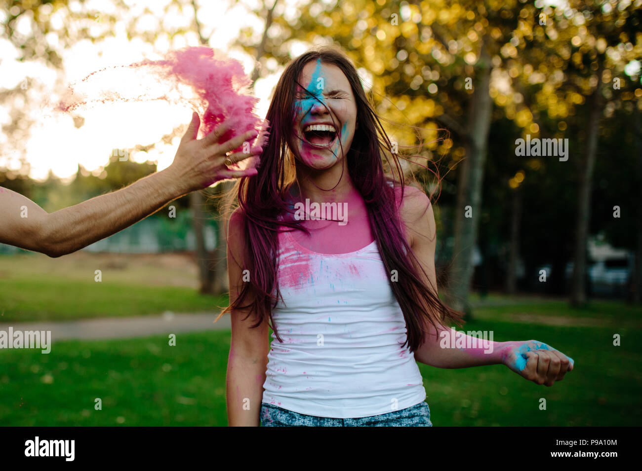 Woman in park laughing while male friend throwing color powder on her face. Friends playing with holi festival at the park. - Stock Image