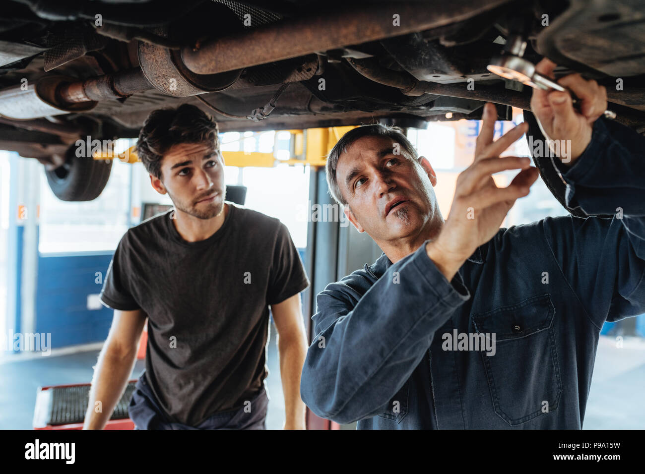 Mature male mechanic discussing and showing something under the car to coworker. Mechanic and male trainee working underneath car together - Stock Image