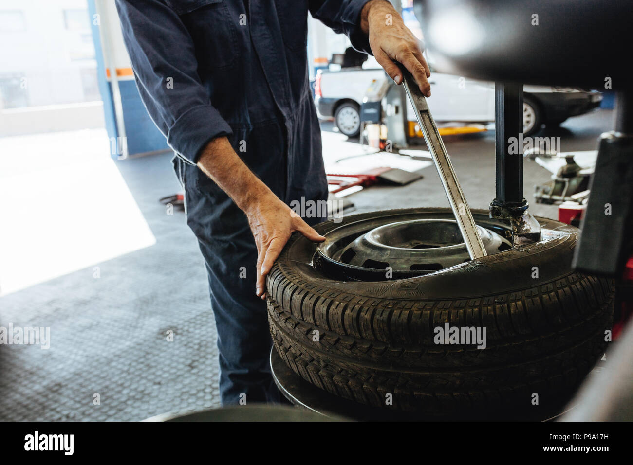 Cropped shot of mechanic removing the tire from rim on machine. Hands of technician taking out the automobile wheel from rim. - Stock Image