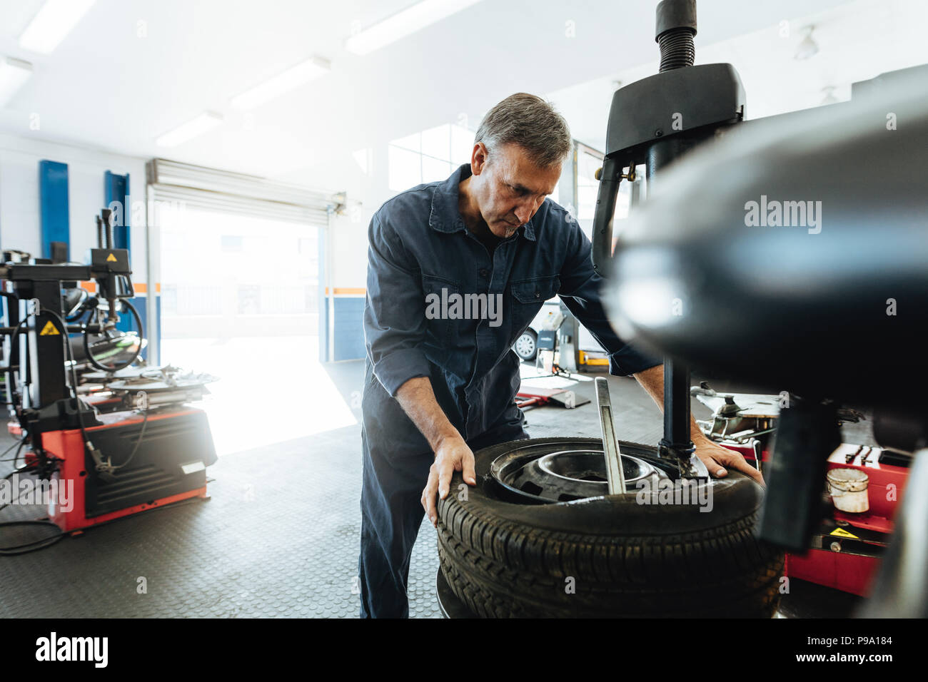 Mature man working in tire service workshop. Mechanic removing tire from wheel on machine. - Stock Image
