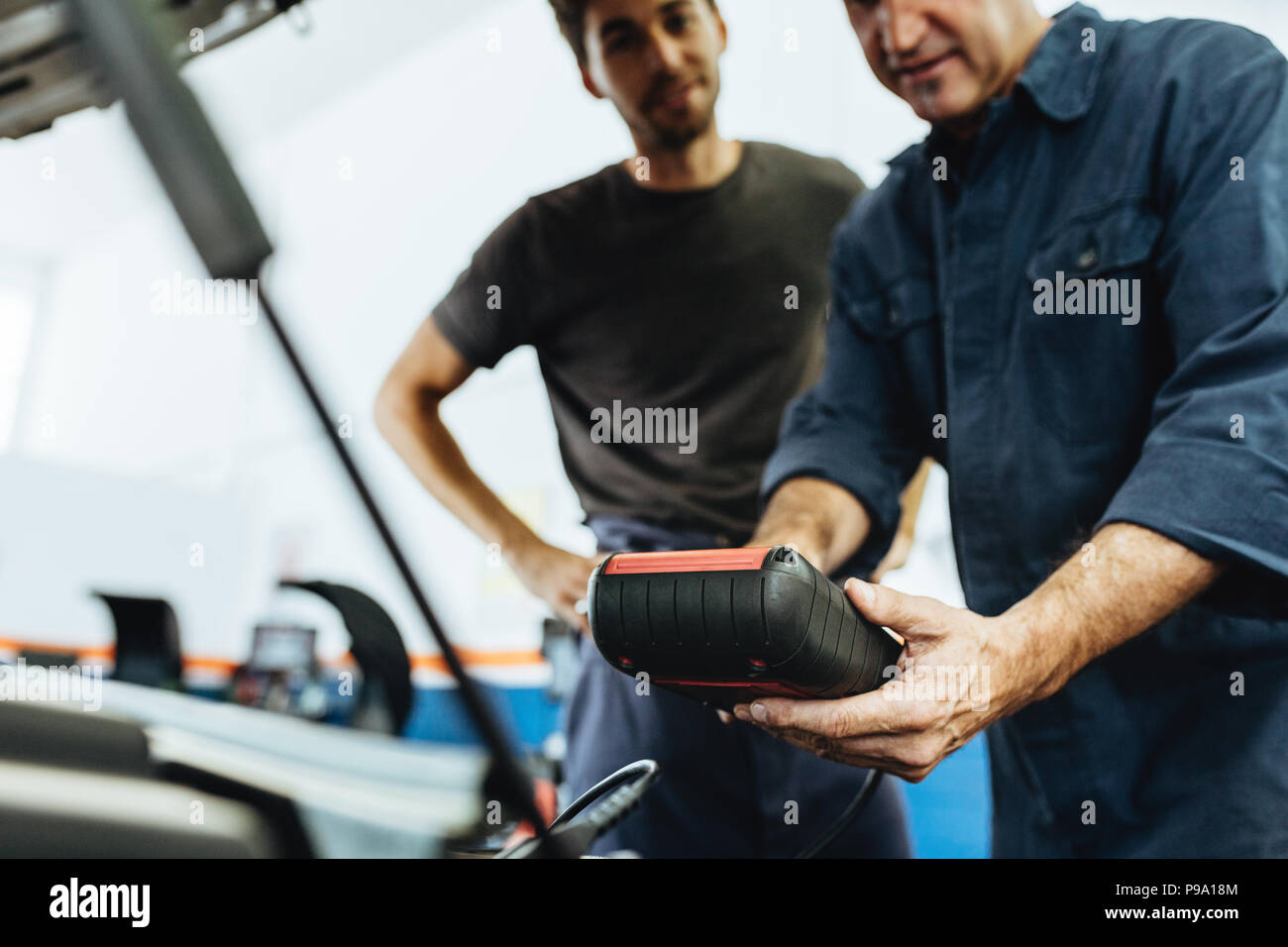 Automobile mechanics holding a device for checking engine condition. Mechanics diagnosing a car engine with device in service station. Stock Photo