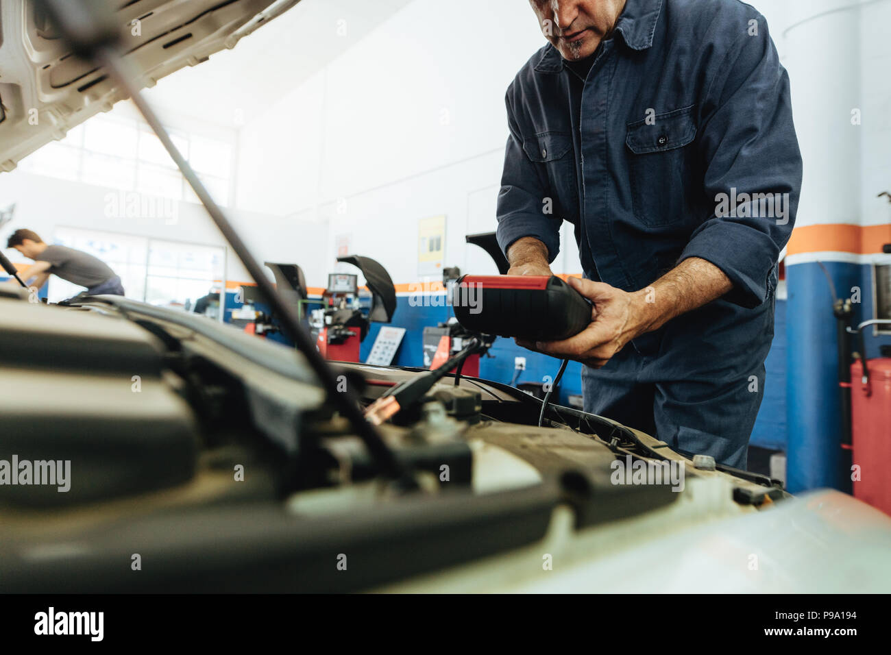 Technician using electronic diagnostic equipment to check the car engine. Mechanics using a device to check the engine. - Stock Image