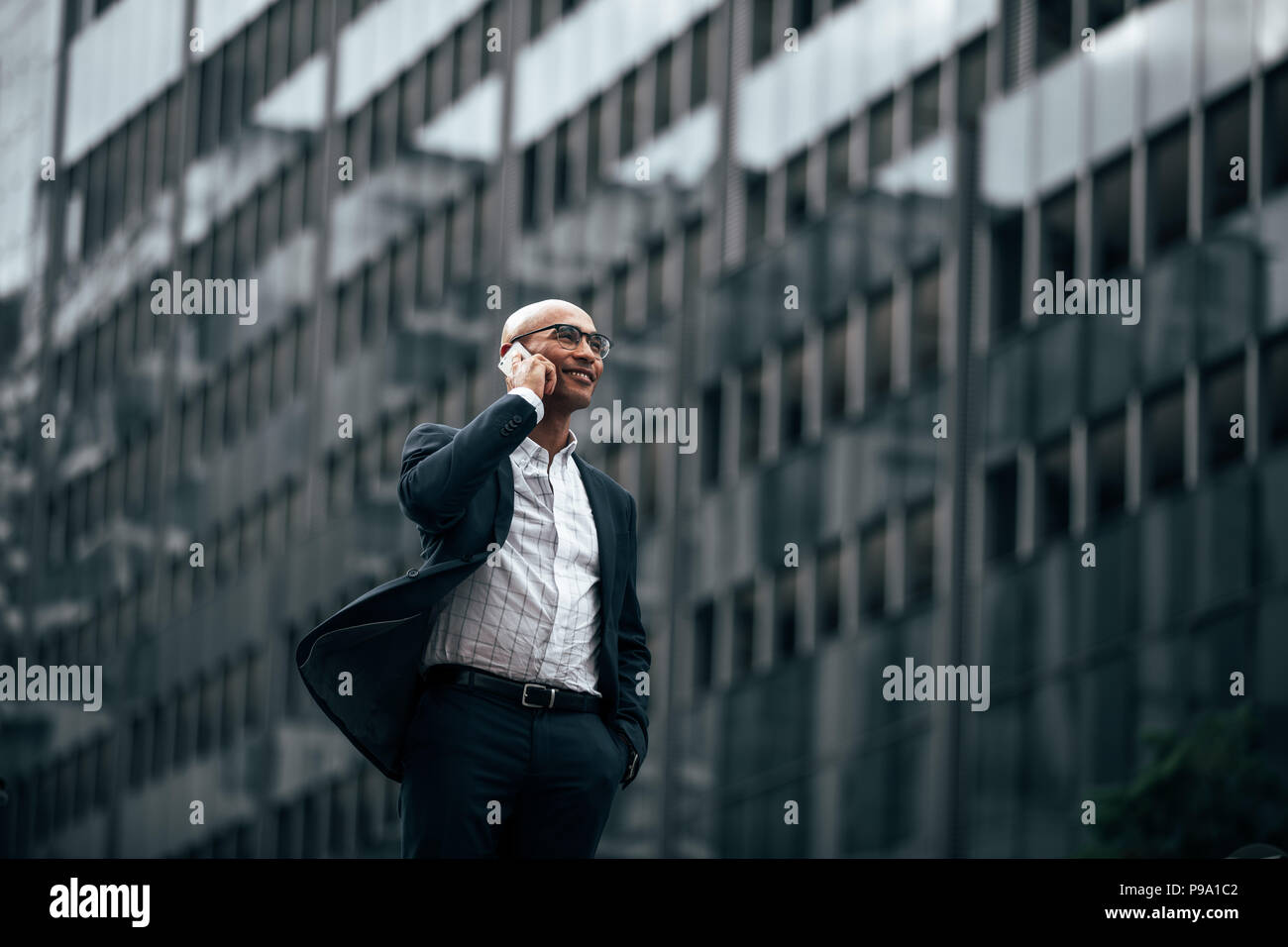Smiling businessman talking over cell phone standing outdoors with a hand in pocket. Man in formal clothes walking on street talking on mobile phone. - Stock Image