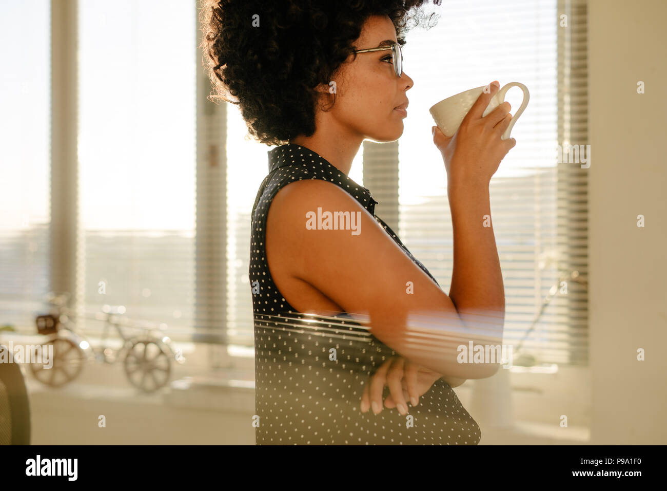 Side view of young businesswoman in casuals drinking coffee in office. Female thinking about something while having coffee during work break. - Stock Image