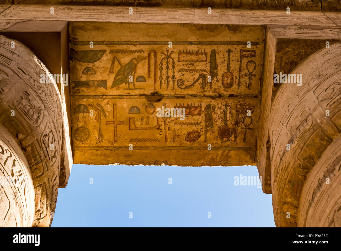 Looking up at colourful painted  Egyptian hieroglyphs at top of columns, great hypostyle hall precinct of Amun Ra, Karnak Temple. Luxor, Egypt, Africa - Stock Image