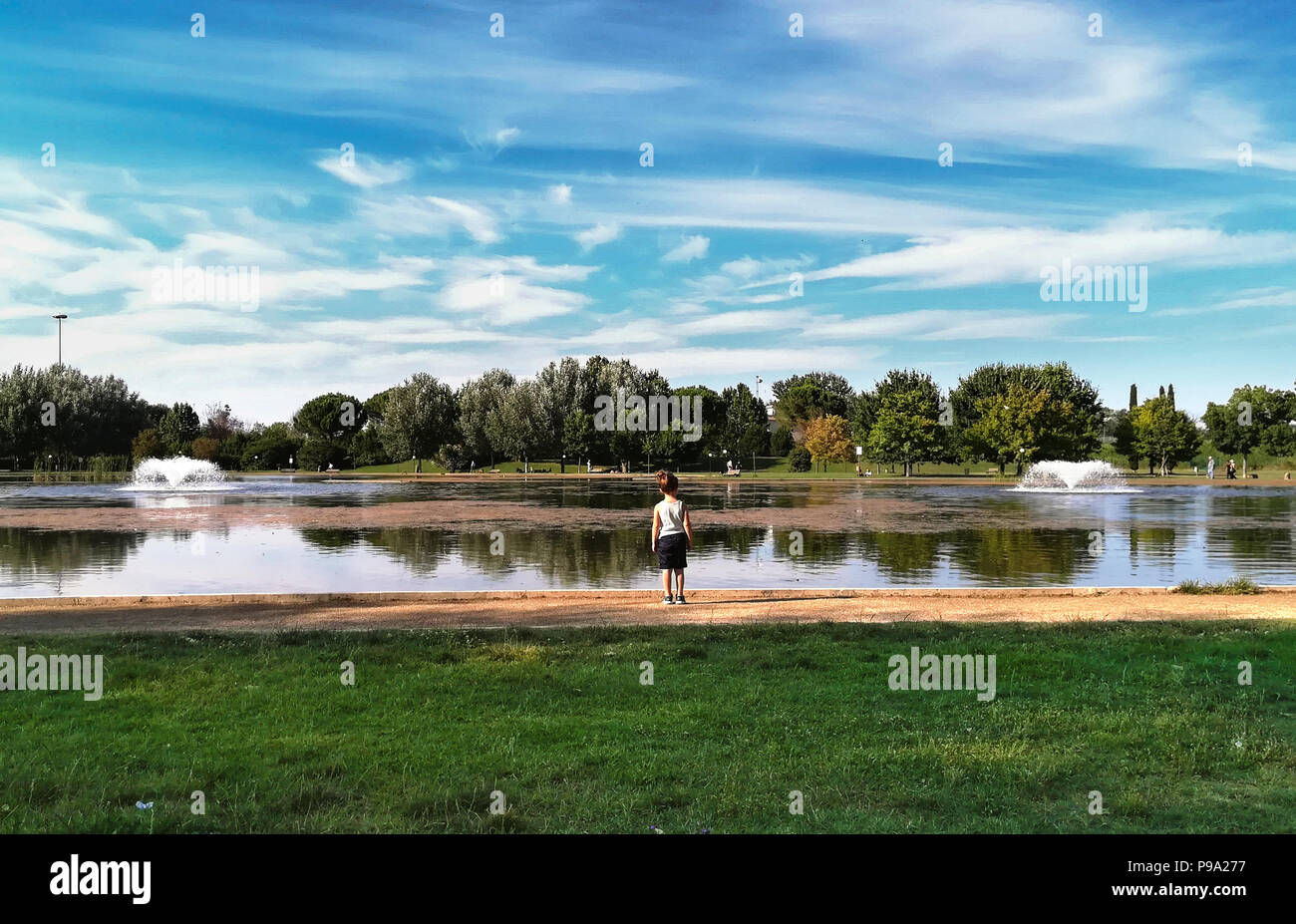 Child rear view looking at tranquil scene lake in urban green park in spring season - Stock Image