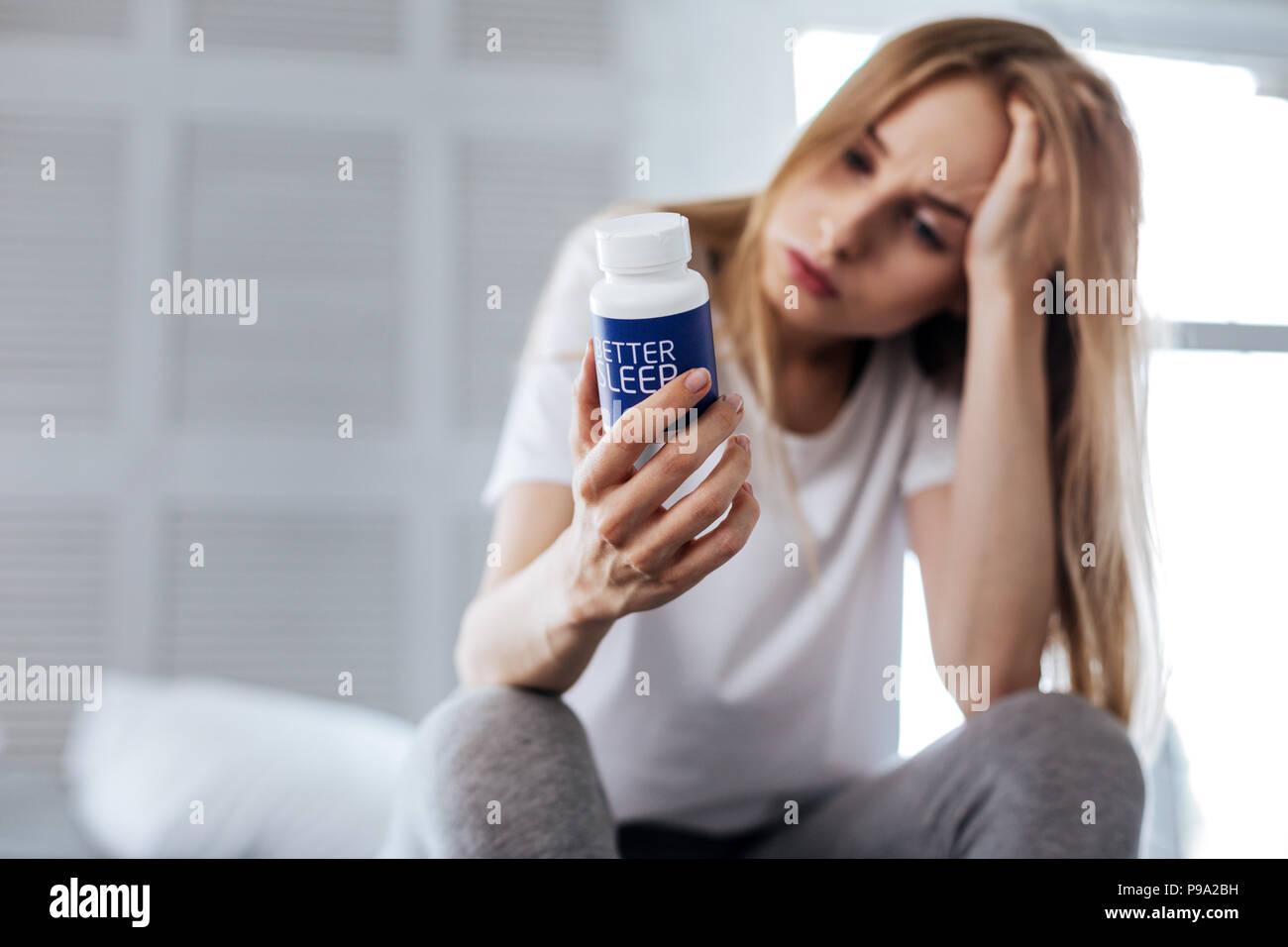 Sad woman looking at her sleeping pills - Stock Image