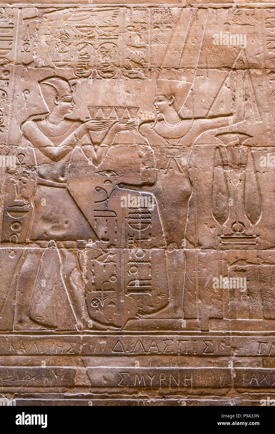 Close up detail of Ancient Egyptian carved figures hieroglyph with Greek script graffiti, Luxor Temple, Luxor, Egypt, Africa - Stock Image