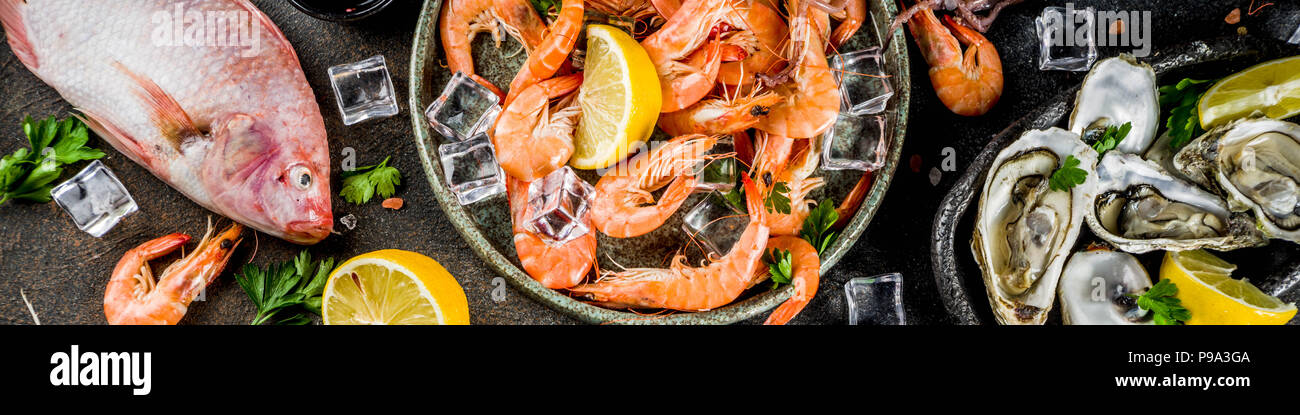 Fresh raw seafood squid shrimp oyster mussels fish with spices of herbs lemon on dark rusty background copy space top view - Stock Image