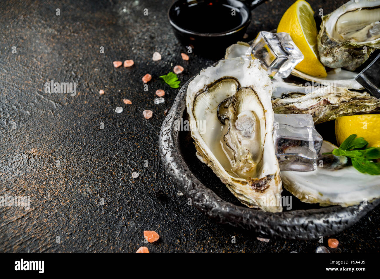 Fresh raw seafood, oysters with lemon and ice on a light blue background - Stock Image