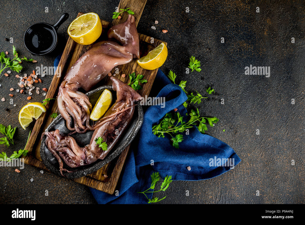 Fresh raw seafood, squid with lemon and light for preparation on a light blue background - Stock Image