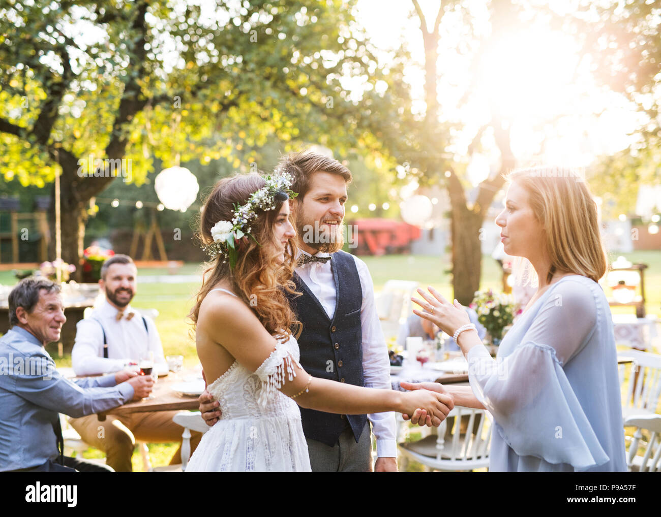 young girl congratulating bride and groom at wedding reception in the backyard