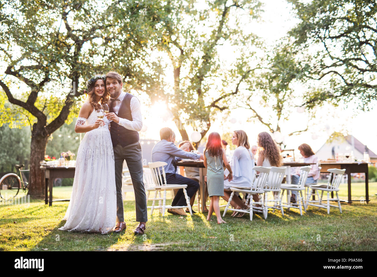 Bride and groom clinking glasses at wedding reception outside in the backyard. - Stock Image