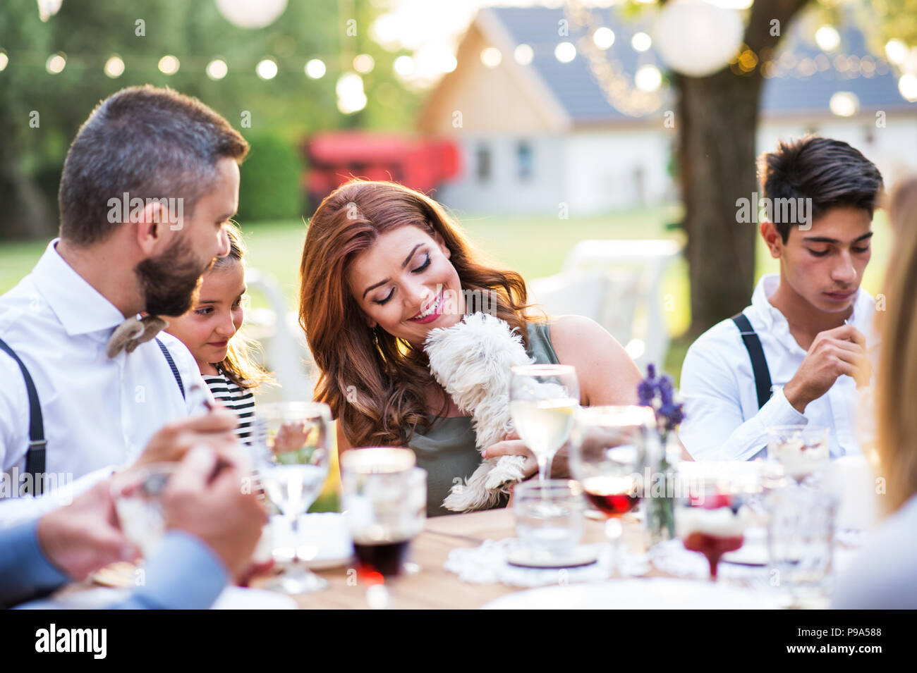 Guests with a small dog sitting at the table outside in the backyard. - Stock Image
