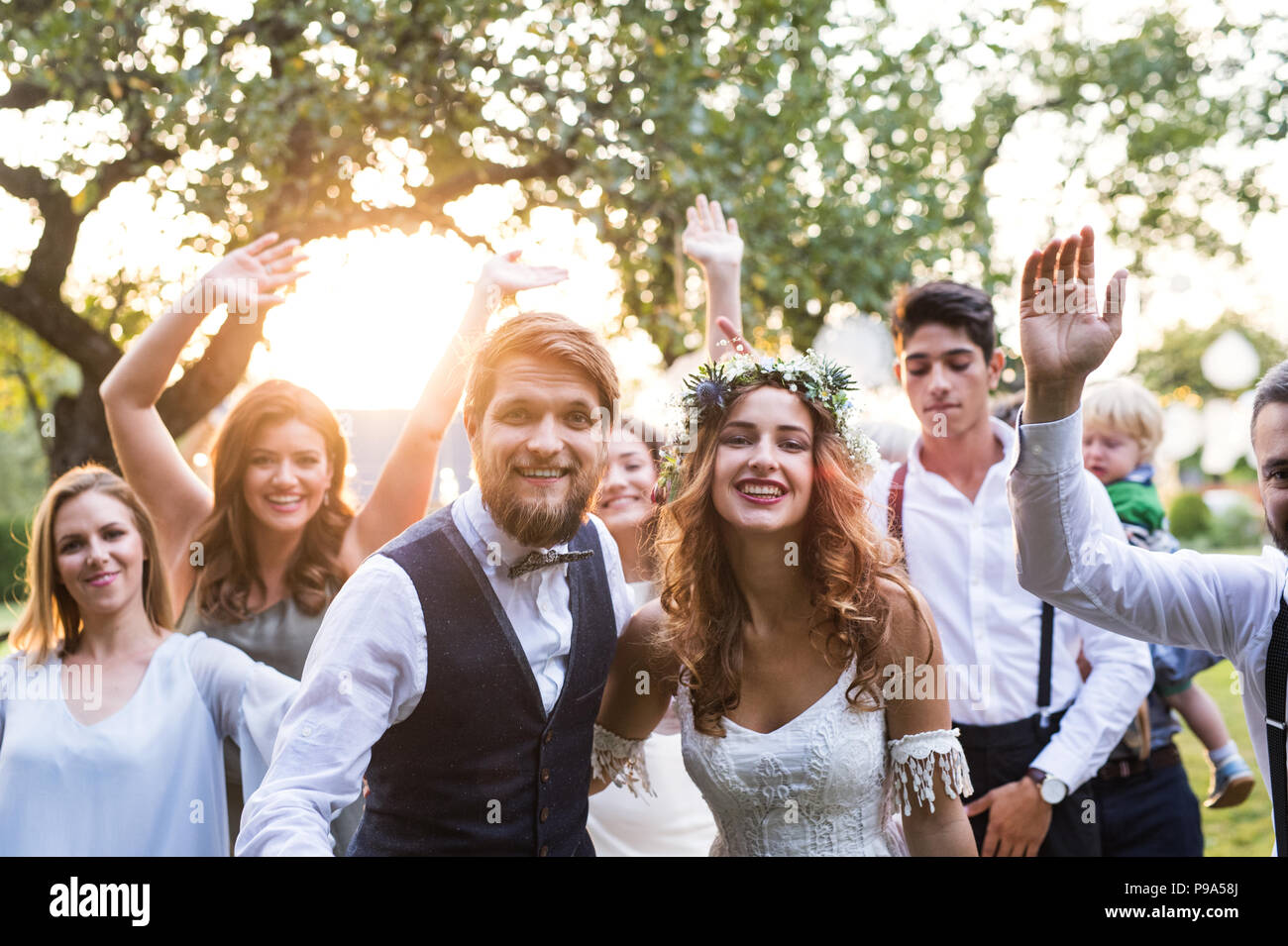 Bride, groom, guests posing for the photo at wedding reception outside in the backyard. - Stock Image