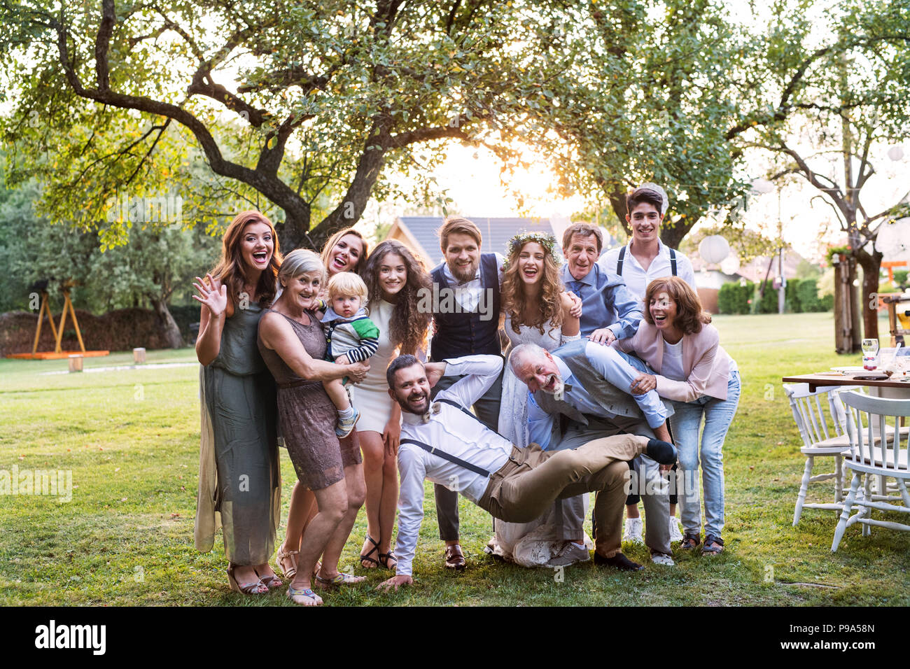 Bride, groom and guests posing for the photo at wedding reception outside in the backyard. - Stock Image